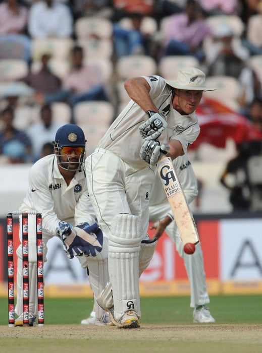 Indian wicketkeeper Mahendra Singh Dhoni (L) watches as New Zealand cricketer Tim McIntosh plays a shot during the first day of the second Test match between India and New Zealand at The Rajiv Gandhi International Cricket Stadium in Hyderabad. (AFP Photo)