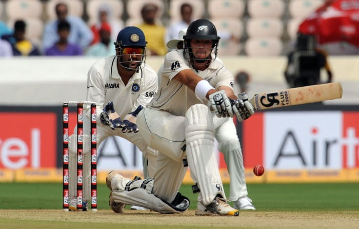 India cricket captain Mahendra Singh Dhoni (L) watches as New Zealand Tim McIntosh plays a shot during the first day of the second Test match between India and New Zealand at The Rajiv Gandhi International Cricket Stadium in Hyderabad. (AFP Photo)