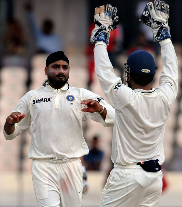 Indian cricketer Harbhajan Singh (L) celebrates the wicket of New Zealand's captain Daniel Vettori with Indian captain Mahendra Singh Dhoni on the second day of the second Test match between India and New Zealand at The Rajiv Gandhi International Cricket Stadium in Hyderabad. (AFP Photo)