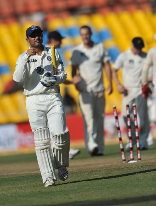 Indian cricketer Virender Sehwag walks towards the pavilion after he was dismissed by New Zealand team captain Daniel Vettori during the first day of the first Test match between India and New Zealand at The Sardar Patel Gujarat Cricket Stadium at Motera on the outskirts of Ahmedabad. (AFP PHOTO)