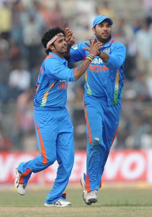 India's Sreesanth (L) and Yuvraj Singh celebrate the dismissal of New Zealand's player Grant Elliott (unseen) during the first one-day International cricket match against New Zealand at Nehru Stadium in Guwahati. (AFP Photo)