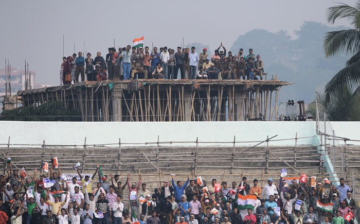 Indian fans watch the first One-Day International between India and New Zealand from a building under construction outside the Nehru Stadium in Guwahati. (AFP Photo)