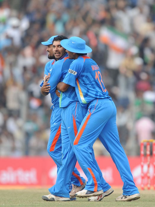 Indian cricketers congratulate teammate Yuvraj Singh (C) after the dismissal of New Zealand's player Grant Elliott (unseen) during the first one-day International cricket match against New Zealand at Nehru Stadium in Guwahati. (AFP Photo)