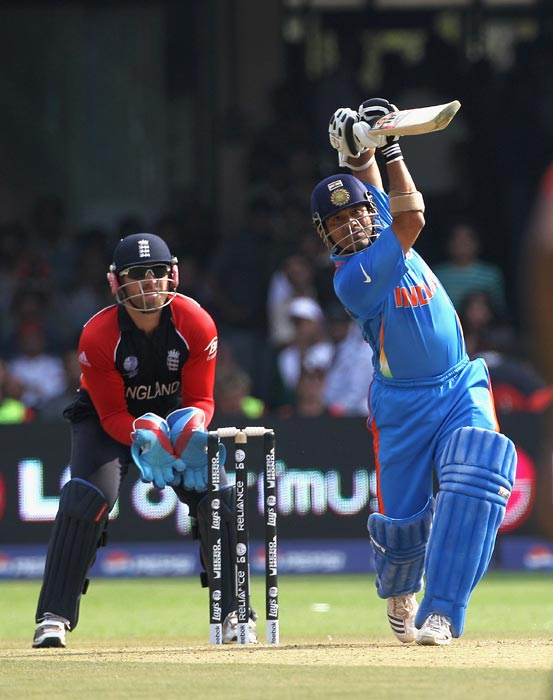 Sachin Tendulkar hits a six over long off with Matt Prior looking on during the 2011 ICC World Cup Group B match between India and England at M. Chinnaswamy Stadium in Bangalore. (Getty Images)