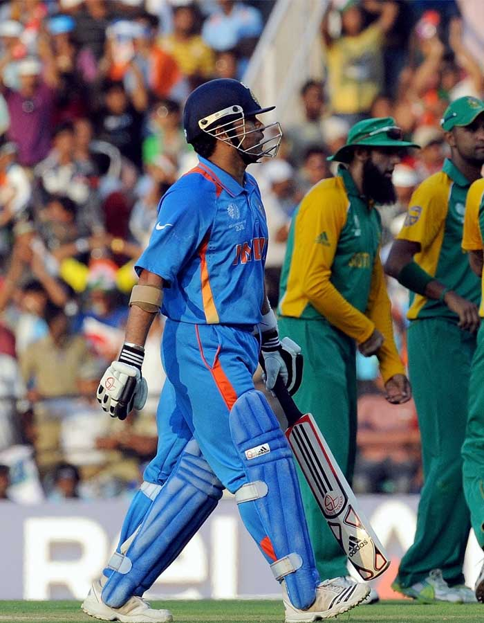 India batsman Sachin Tendukar walks back to the pavillion after his dismissal as South African cricketers celebrate. (AFP Photo)