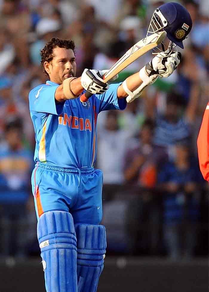 India batsman Sachin Tendulkar raises his bat and helmet after his century. (AFP Photo)