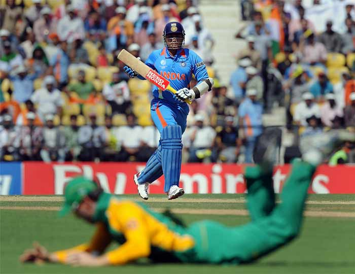 India batsman Virendra Sehwag prepares to take a run as South African fielder Johan Botha successfully fields the ball. (AFP Photo)