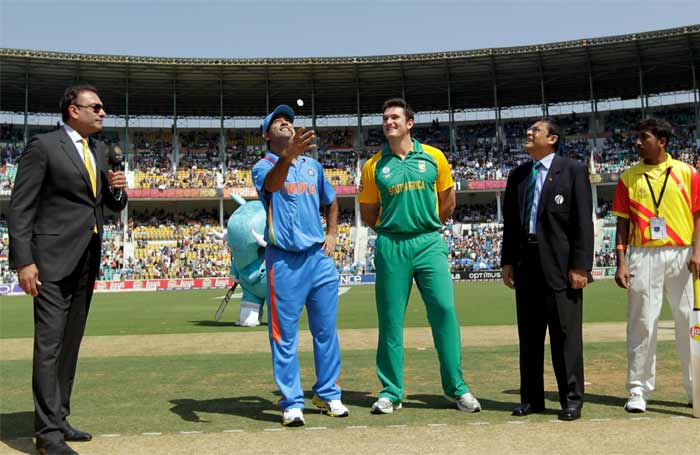 MS Dhoni of India takes the coin toss as Graeme Smith of South Africa looks on during the Group B ICC World Cup Cricket match between India and South Africa. (AFP Photo)
