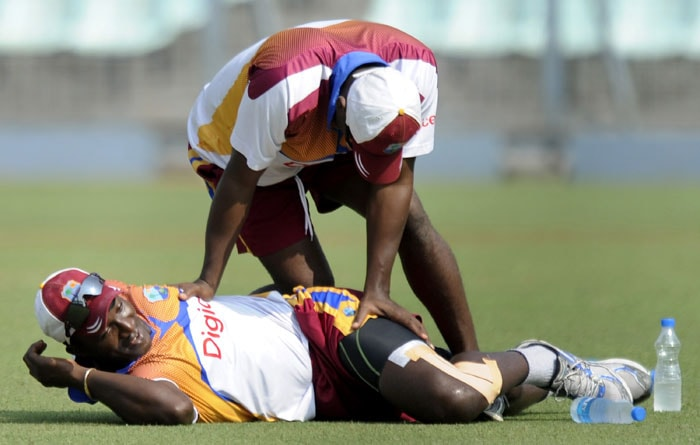 West Indies cricket captain Darren Sammy on the ground is attended by a support staff during a training session at the Eden Gardens. (AFP Photo)