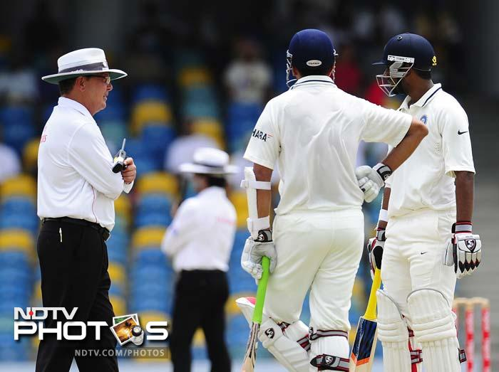 Rahul Dravid (C), Abhinav Mukund and umpire Ian Gould await a third umpire's decision to decide if Dravid was caught out. (AFP Photo)