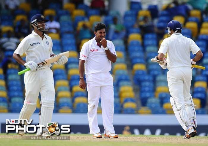 VVS Laxman and Rahul Dravid run bewteen the wickets during their partnership of 65 runs as Ravi Rampaul looks on. (AFP Photo)