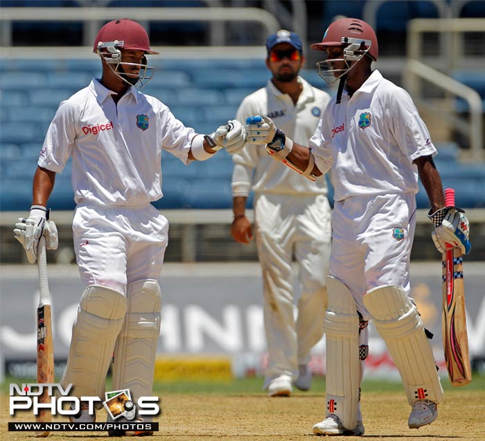 Carlton Baugh is congratulated by his batting partner Shivnarine Chanderpaul after hitting a six off Harbhajan Singh.