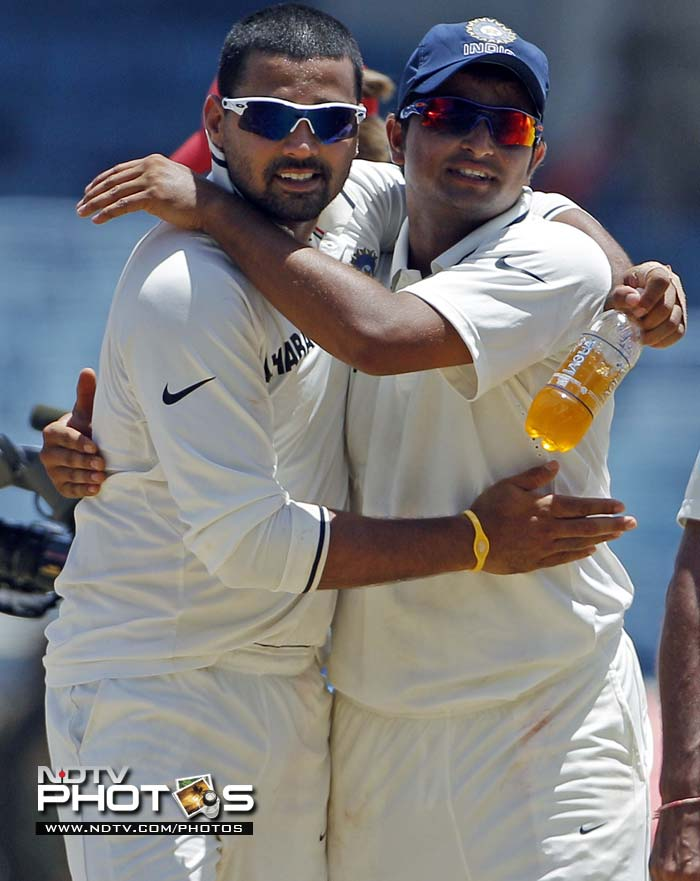 Murali Vijay, left, and Suresh Raina hug while celebrating the victory over the West Indies by 63 runs on the fourth day of their first Test match.