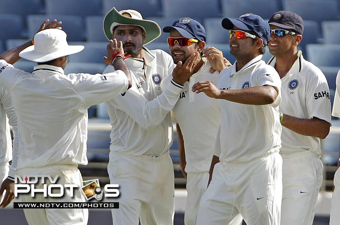 India's Virat Kohli, center, is congratulated by teammates after taking the catch to dismiss West Indies' batsman Ramnaresh Sarwan for a duck in the second innings on the third day of the Test match.