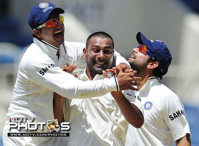 Indian bowler Praveen Kumar (C) celebrates with Suresh Raina (L) and Virat Kohli after taking the wicket of West Indies batsman Shivnarine Chanderpaul during the fourth day of the first Test match.