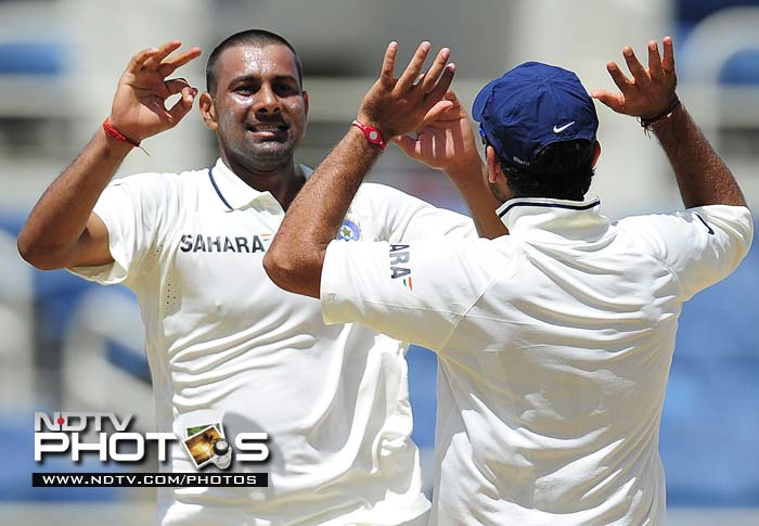 Praveen Kumar celebrates with teammate Virat Kohli after picking up the wicket of Darren Bravo on the fourth day of the first Test match.