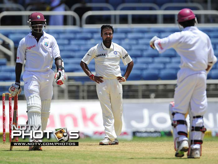 Amit Mishra (C) looks at West Indies batsmen Fidel Edwards (L) as he puts up a fight with Devendra Bishoo for the last wicket, during the fourth day of the first Test match.