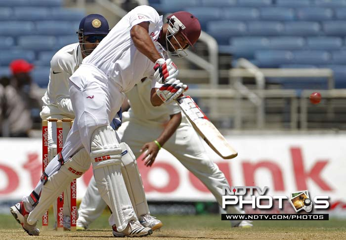 West Indies batsman Ravi Rampaul hits a six off India's Harbhajan Singh as wicket keeper Mahendra Singh Dhoni looks on in the second innings during the fourth day of their first Test match.