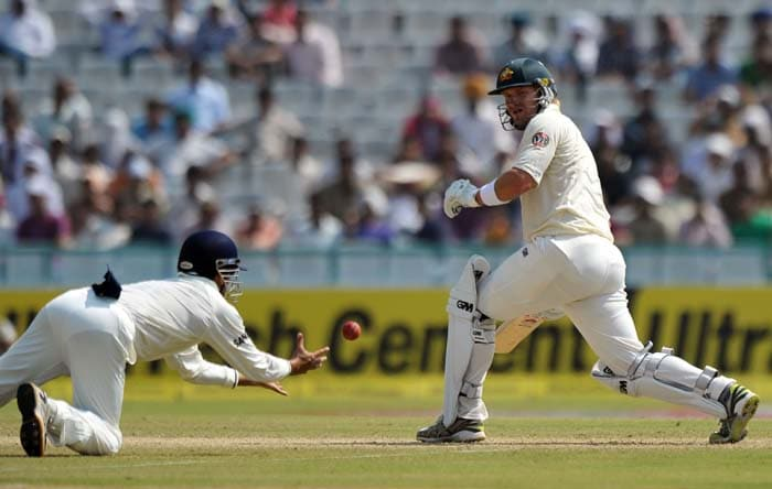Indian fielder Gautam Gambhir dives to take the catch of Australian cricket player Shane Watson during the second day of the first Test between India and Australia in Mohali. (AFP Photo)