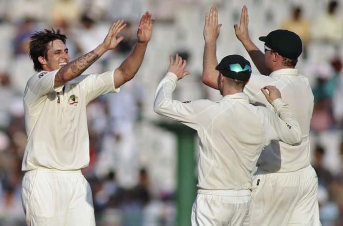 Australia's Mitchell Johnson, celebrates with teammates the dismissal of India's Virender Sehwag during the second day of the first Test between India and Australia in Mohali. (AFP Photo)