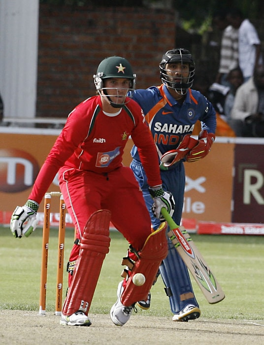 Zimbabwean Batsman Brendan Taylor defends the ball as Indian wicket keeper Dinesh Karthik looks on. (AFP Photo)