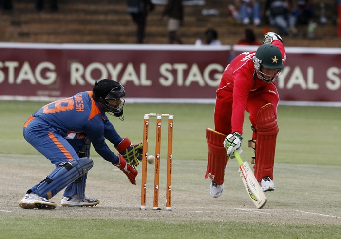 Zimbabwean Batsman Brendan Taylor completes a run as Indian wicket keeper Dinesh Karthik tries unsuccessfully to run him out. (AFP Photo)