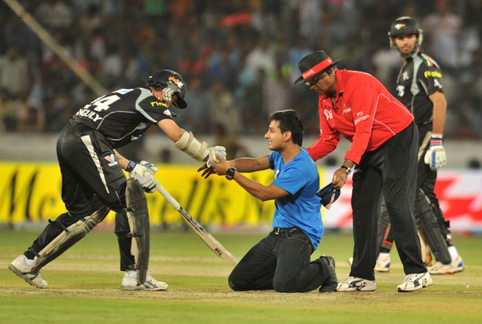 An unidentified spectator reacts after touching the feet of Sourav Ganguly in a sign of respect after running onto the pitch during the IPL Twenty20 match between Deccan Chargers and Pune Warriors at the Rajiv Gandhi International Stadium in Hyderabad. (AFP Photo)