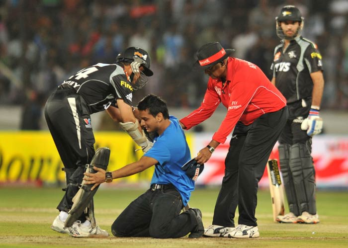 An unidentified spectator touches the feet of Sourav Ganguly in a sign of respect after running onto the pitch during the IPL Twenty20 match between Deccan Chargers and Pune Warriors at the Rajiv Gandhi International Stadium in Hyderabad. (AFP Photo)