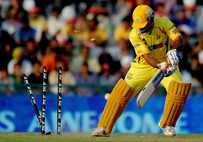 Chennai Super Kings captain Mahendra Singh Dhoni is bowled out by Kings XI Punjab bowler Ryan Harris during the IPL Twenty20 match at the Punjab Cricket Association (PCA) Stadium in Mohali. (AFP PHOTO)