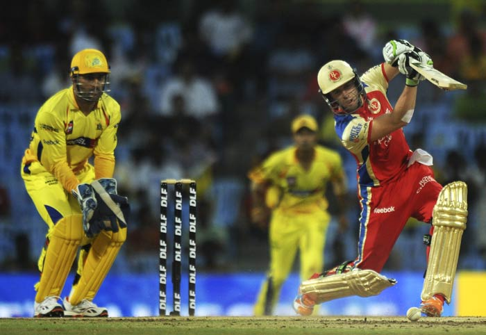 AB de Villiers is watched by Mahendra Singh Dhoni as he plays a shot during the IPL Twenty20 match between Chennai Super Kings and Royal Challengers Bangalore at the M.A. Chidambaram Stadium in Chennai. (AFP Photo)