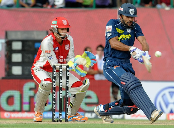 Adam Gilchrist looks on as Shikhar Dhawan plays a shot during the IPL cricket match between Deccan Chargers Hyderabad and Kings XI Punjab at the Himachal Pradesh Cricket Association Stadium in Dharamsala. (AFP Photo)