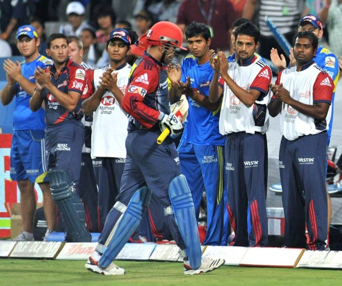 Delhi Daredevils captain Virender Sehwag walks back as his teammates congratulate him on scoring a century (100 runs) during the IPL Twenty20 match against the Deccan Chargers at the Rajiv Gandhi International Stadium in Hyderabad. Delhi Daredevils won by 4 wickets. (AFP Photo)