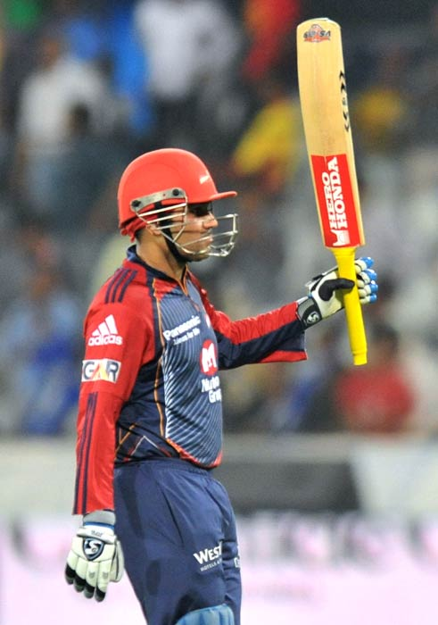 Virender Sehwag raises his bat while walking back to pavilion after scoring a century during the IPL Twenty20 match between the Delhi Daredevils and the Deccan Chargers at the Rajiv Gandhi International Stadium in Hyderabad. (AFP Photo)