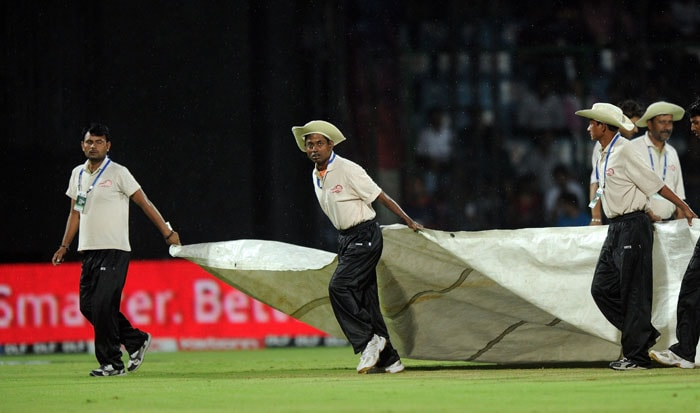 Groundstaff cover the pitch as it rains during the IPL Twenty20 match between Delhi Daredevils and Pune Warriors at the Feroz Shah Kotla stadium in New Delhi. (AFP Photo)