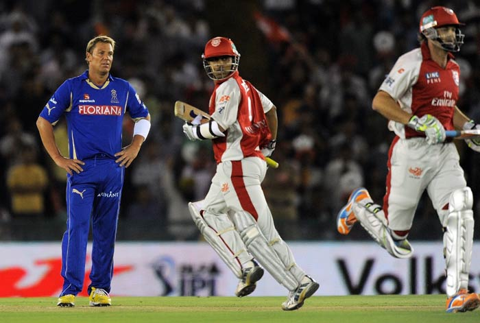 Shane Warne watches as Adam Gilchrist and teammate Paul Valthaty run between the wickets during the IPL Twenty20 match between Rajasthan Royals and Kings XI Punjab at the Punjab Cricket Association stadium in Mohali. (AFP Photo)