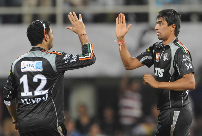 Rahul Sharma celebrates with captain Yuvraj Singh after taking the wicket of Rohit Sharma during the IPL Twenty20 match between Pune Warriors and Mumbai Indians at the D.Y. Patil Cricket stadium in the outskirts of Mumbai. (AFP Photo)