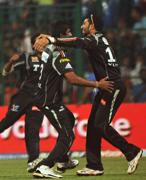 Rahul Sharma with teammate Yuvraj Singh celebrate the wicket of Chris Gayle during the IPL Twenty20 match between Pune Warriors and Royal Challengers Bangalore at the M.Chinnaswamy Stadium in Bangalore. (AFP Photo)