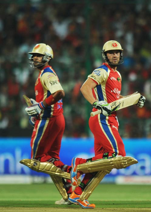 AB de Villiers and Virat Kohli run between wickets during the IPL Twenty20 match between Pune Warriors and Royal Challengers Bangalore at the M.Chinnaswamy Stadium in Bangalore. (AFP Photo)