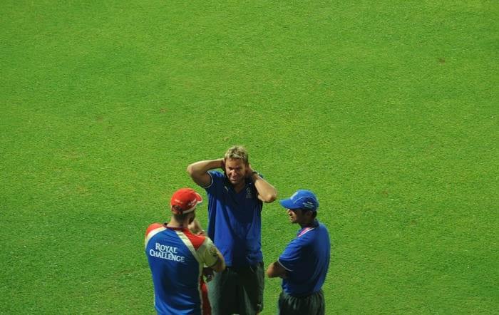 Rajasthan Royals skipper Shane Warne talks with his teammate Rahul Dravid and Royal Challengers Bangalore captain Daniel Vettori as rain delayed the start of the IPL Twenty20 match between Rajasthan Royals and Royal Challengers Bangalore at the M.Chinnaswamy Stadium in Bangalore. (AFP Photo)