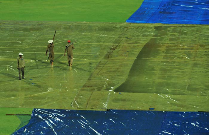 Groundstaff work to clear water from the tarp covering the ground as rain delayed the start of the IPL Twenty20 match between Rajasthan Royals and Royal Challengers Bangalore at the M.Chinnaswamy Stadium in Bangalore. (AFP Photo)