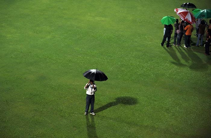 An official inspects the ground as rain delayed the start of the IPL Twenty20 match between Rajasthan Royals and Royal Challengers Bangalore at the M.Chinnaswamy Stadium in Bangalore. (AFP Photo)