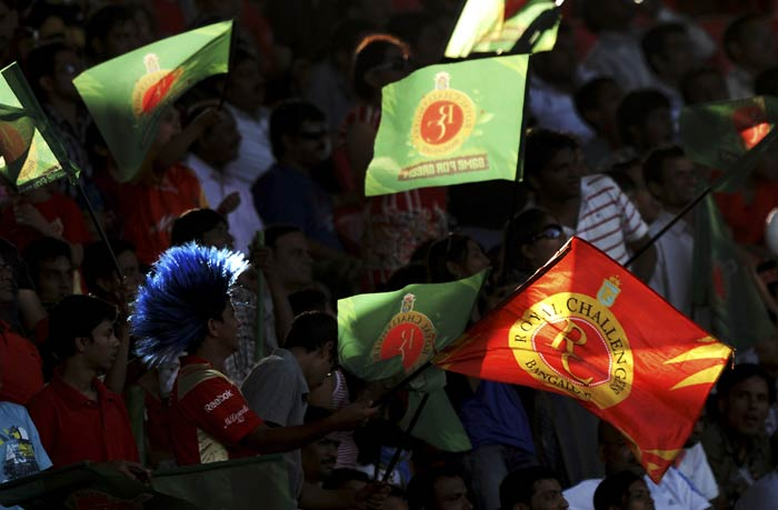 Royal Challengers Bangalore supporters wave team's flag during their IPL Twenty20 match against Kochi Tuskers Kerala at the M.Chinnaswamy Stadium in Bangalore. (AFP Photo)