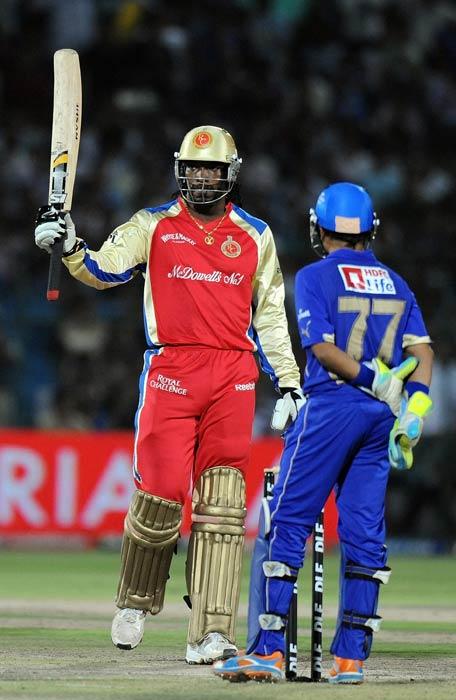 Chris Gayle raises his bat after his half-century during the IPL Twenty20 match between Rajasthan Royals and Royal Challengers Bangalore at the Sawai Mansingh Stadium in Jaipur. (AFP Photo)