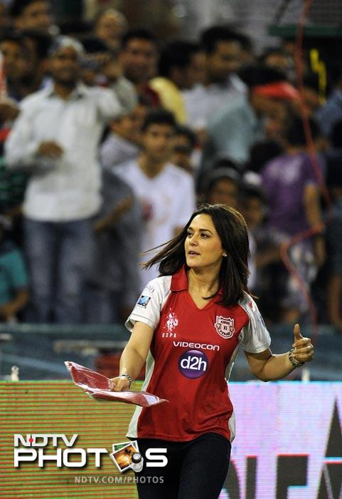 Kings XI Punjab team owner and Bollywood actress Preity Zinta distributes T-Shirts to spectators during the IPL Twenty20 match between Kings XI Punjab and Pune Warriors at PCA Stadium in Mohali. (AFP Photo)