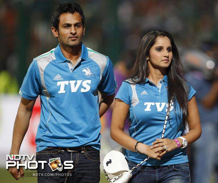 Indian tennis player Sania Mirza and her husband and Pakistani cricketer Shoaib Malik walk before the start of the IPL match between Pune Warriors and Royal Challengers Bangalore in Bangalore. (AP Photo)