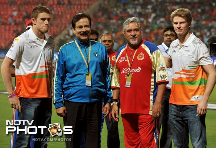 Joint owners of Sahara Force India Formula One team, Subrata Roy Sahara, who also owns Sahara Pune Warriors team, and Dr Vijay Mallya, who also owns Royal Challengers Bangalore, pose with their race drivers Paul di Resta and Nico Hulkenberg prior to the IPL Twenty20 between Royal Challengers Bangalore and Pune Warriors at the M. Chinnaswamy Stadium in Bangalore. (AFP Photo)