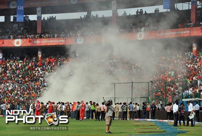 Smoke caused by a fire in an electrical short circuit blows towards spectators in the gallery prior to the IPL Twenty20 match between Royal Challenger Bangalore and Kolkata Knight Riders at the M. Chinnaswamy Stadium in Bangalore. (AFP Photo)