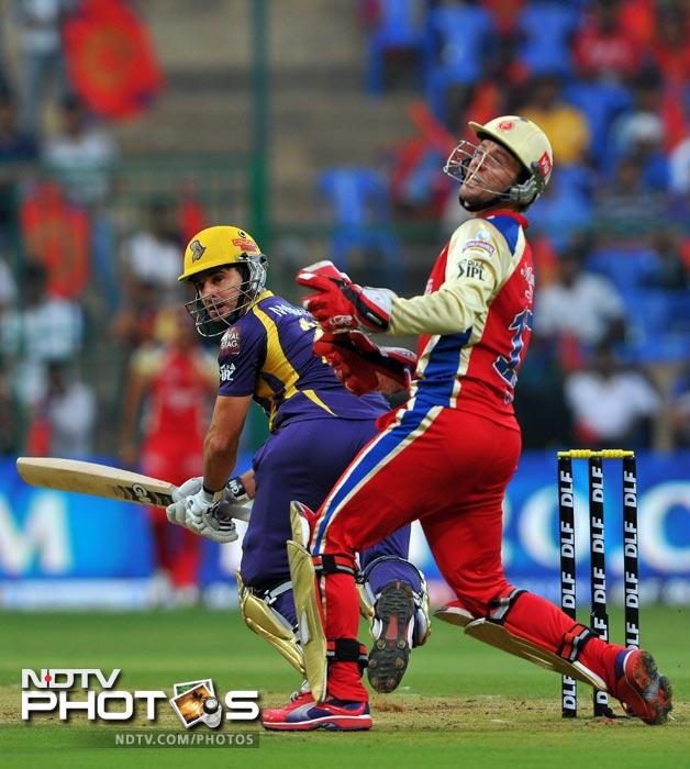 Ryan ten Doeschate plays a shot while AB de Villers looks on during the IPL Twenty20 match between Royal Challengers Bangalore and Kolkata Knight Riders at the M. Chinnaswamy Stadium in Bangalore. (AFP Photo)