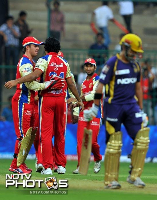 Royal Challengers Bangalore players congratulate Zaheer Khan while Gautam Gambhir walks back to the pavilion after being caught out during the IPL Twenty20 match between Royal Challenger Bangalore and Kolkata Knight Riders at the M. Chinnaswamy Stadium in Bangalore. (AFP Photo)