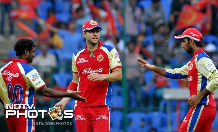 Cheteshwar Pujara and Daniel Vettori congratulate teammate Muttiah Muralidaran after he took the wicket of Manvinder Bisla during the IPL Twenty20 match between Royal Challengers Bangalore and Kolkata Knight Riders at the M. Chinnaswamy Stadium in Bangalore. (AFP Photo)
